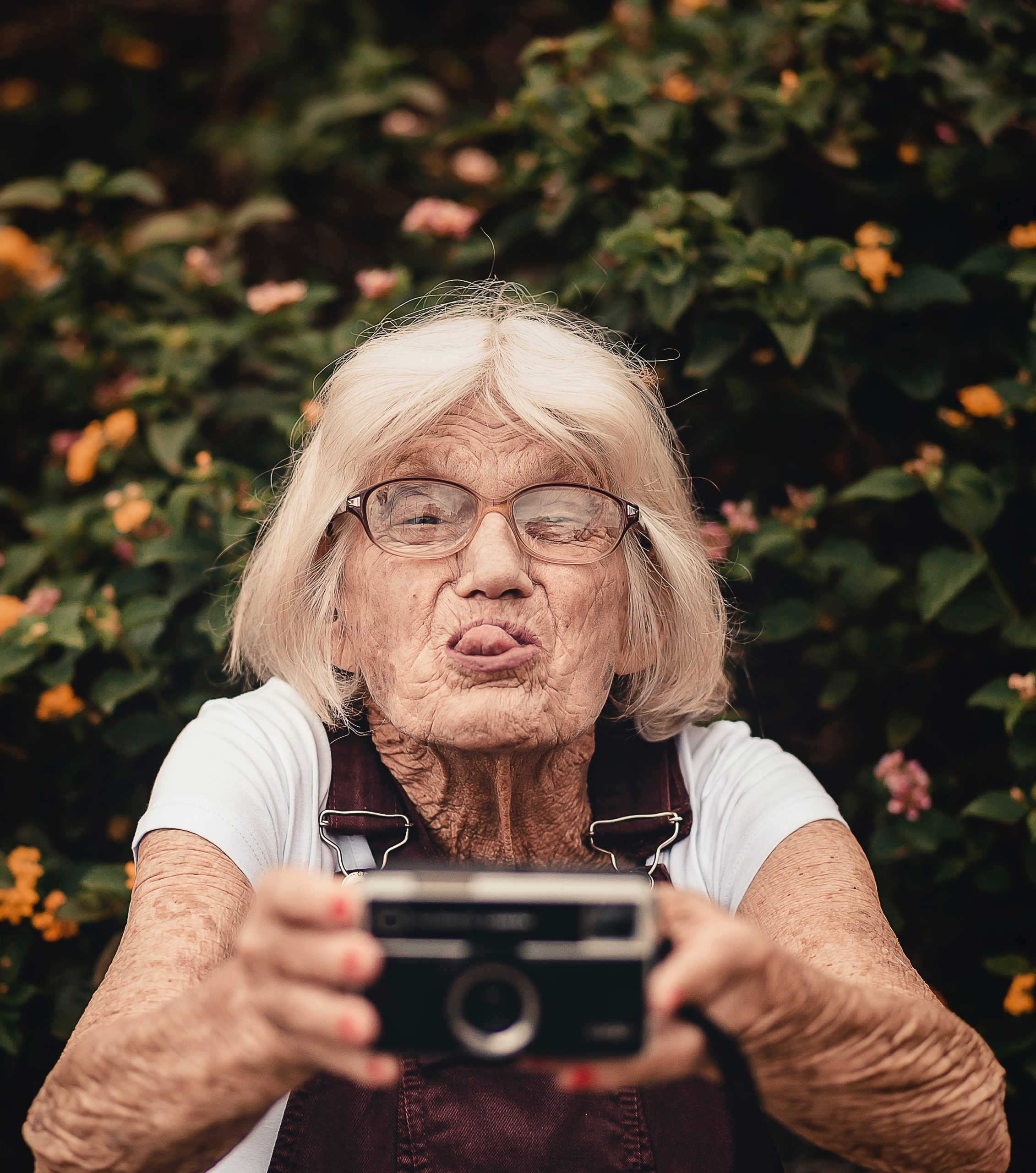 Older woman taking selfie with old camera